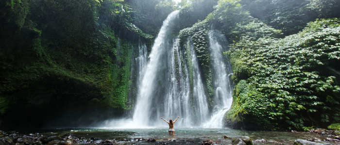girl standing under bali waterfall