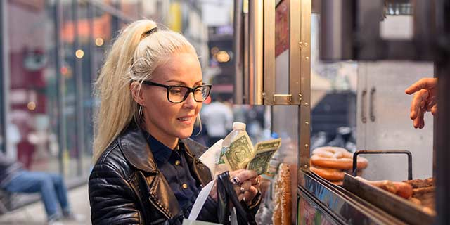 Lady paying with cash at food vendor