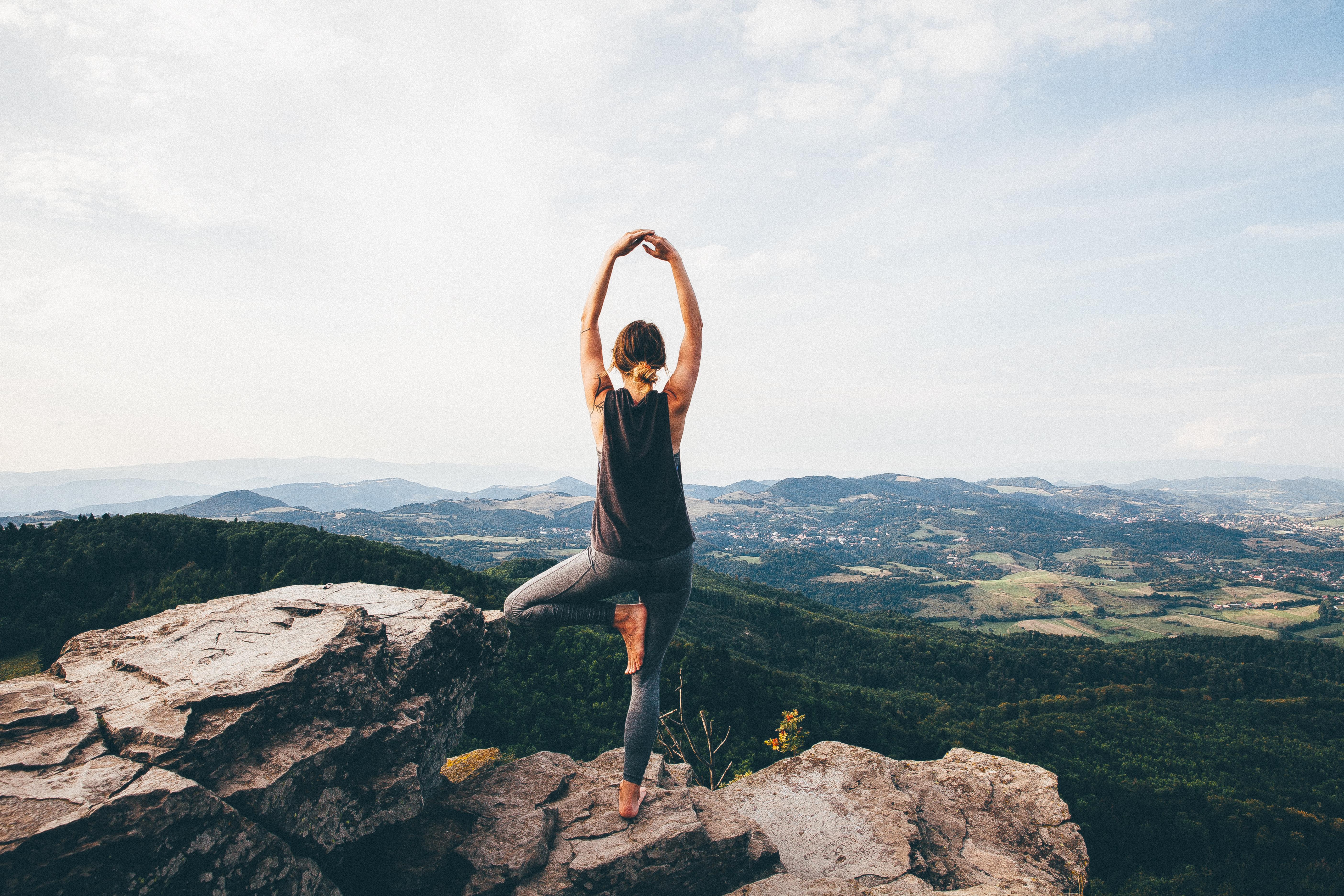 Girl does yoga overlooking canyon