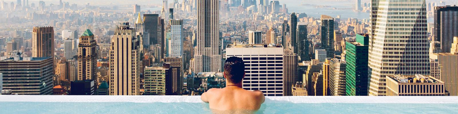 man in swimming pool overlooking city view
