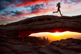 female running on rock in Utah at sunset