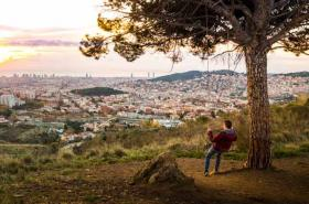 Man on swing looking over Spanish city