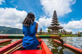 Lady in blue dress looking at temple in Bali